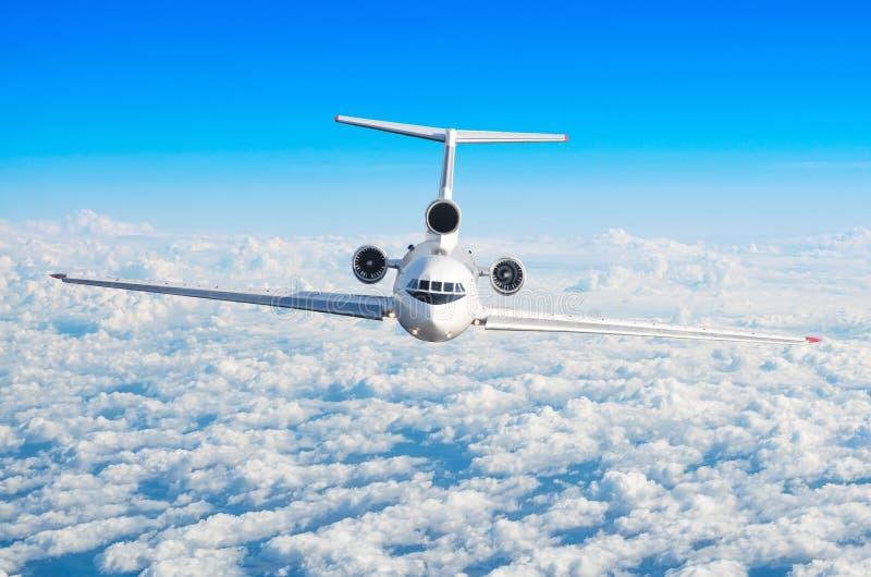 Passagiersvliegtuig met drie motoren op de staart die bij vliegniveau hoog in de hemel boven de wolken en de blauwe hemel vliegen royalty-vrije stock fotografie