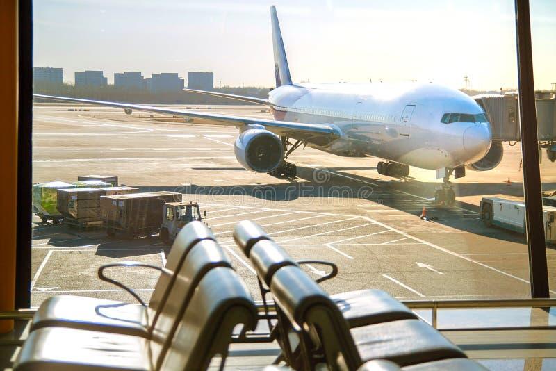 Passagiersvliegtuigen bij de luchthaven, mening door venster stock afbeelding