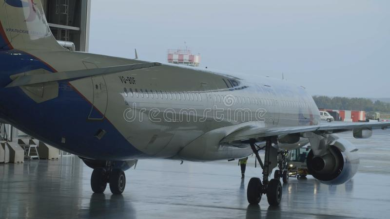 Passagiersvliegtuigen, onderhoudend motoren en reparatie die van de fuselage, de hangaar van de luchthaven verlaten Luchtbus voor stock afbeeldingen