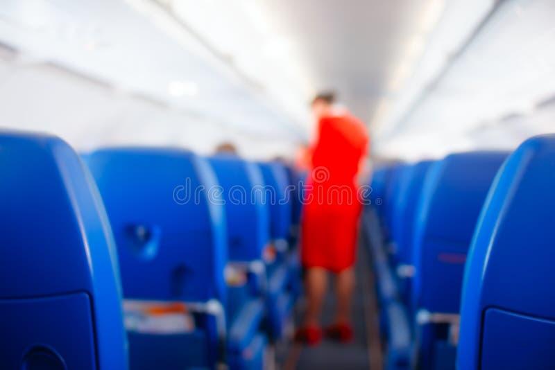 Passagierszetel, Binnenlands van vliegtuig met passagiers op zetels zitten en stewardess die de doorgang op achtergrond lopen ste stock afbeeldingen