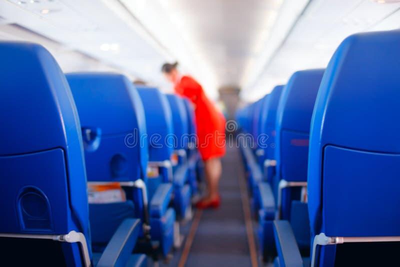 Passagierszetel, Binnenlands van vliegtuig met passagiers op zetels zitten en stewardess die de doorgang op achtergrond lopen ste stock foto