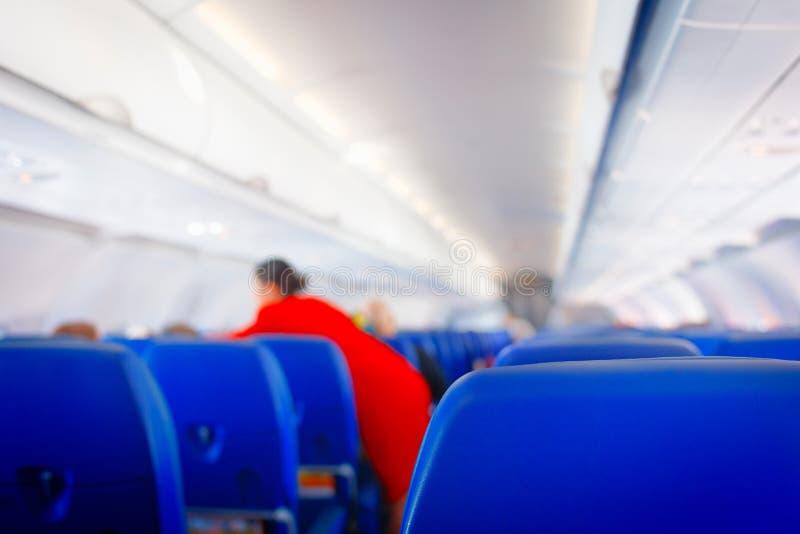 Passagierszetel in vliegtuig, Binnenlands van vliegtuig en stewardessachtergrond De stewardess geeft de diensten voor passagiers  stock foto's