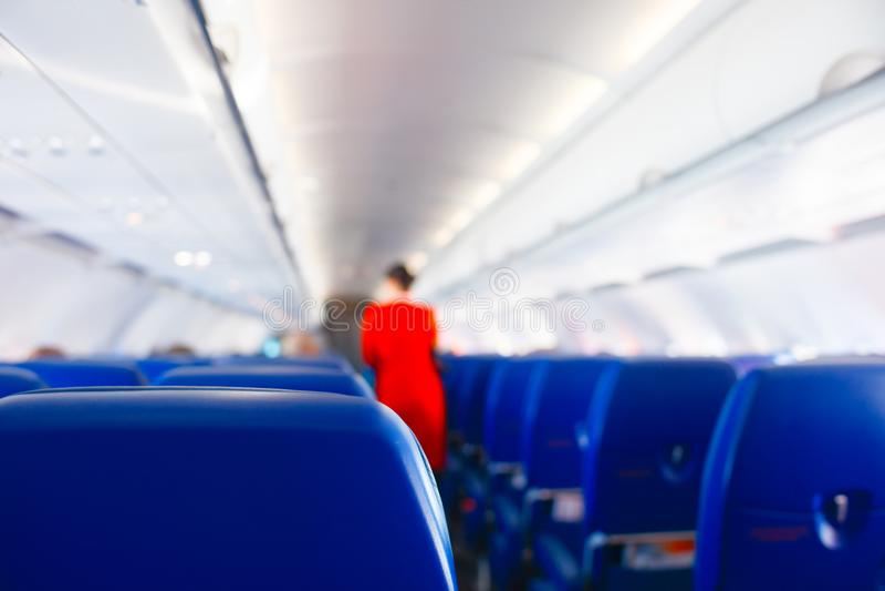 Passagierszetel in vliegtuig, Binnenlands van vliegtuig en stewardessachtergrond De stewardess geeft de diensten voor passagiers  stock afbeeldingen