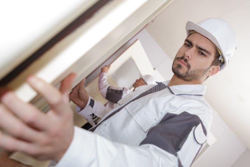 Passande fönster för ung byggnadsarbetare fotografering för bildbyråer