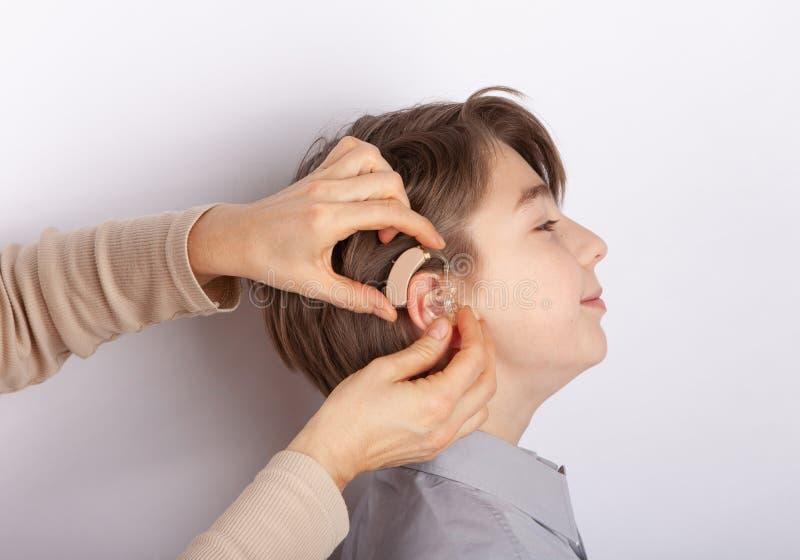 Passande hörapparat för Audiologist på en smilling unga pojkes öra arkivbild