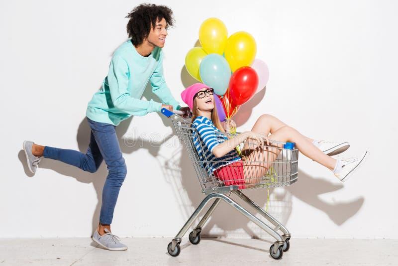 Passando o grande tempo junto Homem novo feliz que leva sua amiga bonita no carrinho de compras e que sorri ao correr contra foto de stock
