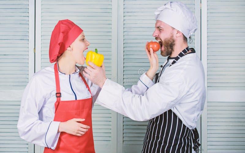 Passando o tempo agrad?vel em casa vegetariano Uniforme do cozinheiro cozinheiro chefe do homem e da mulher no restaurante pares  foto de stock royalty free