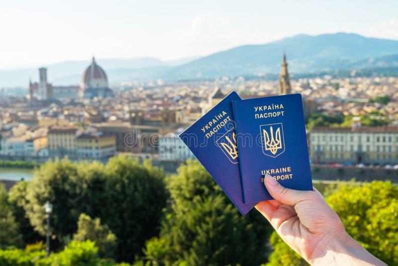 Passaporte biométrico azul ucraniano com microplaqueta da identificação sobre contra o fundo de Florença foto de stock royalty free