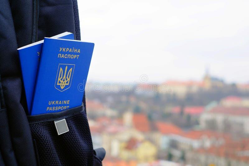 Passaporte biométrico azul ucraniano novo com microplaqueta da identificação sobre contra o fundo da cidade fotografia de stock
