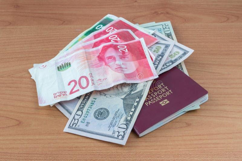 Passaporte biométrico polonês com as cédulas do dólar de Estados Unidos e as cédulas novas israelitas do shekel imagens de stock