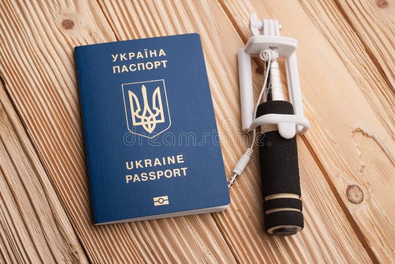 Passaporte biométrico ucraniano com a vara do selfi no fundo de madeira imagens de stock royalty free