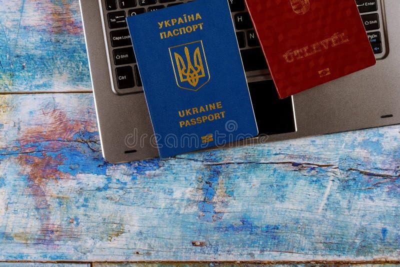 Passaporte biométrico ucraniano e passaporte húngaro no teclado de computador, preenchendo o documento que solicita o registro imagem de stock