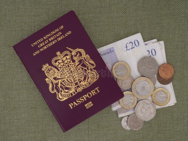 Passaporte BRIT?NICO novo de Bergundy, j? n?o mostrando palavras ?Uni?o Europeia ? Com moeda, libras esterlinas No fundo de pano fotografia de stock