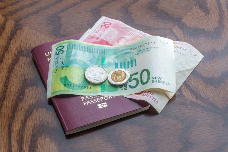 Passaporte com as cédulas e as moedas novas israelitas do shekel na tabela de madeira fotografia de stock
