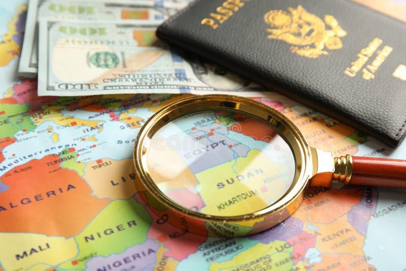 Passaporte, dinheiro e lente de aumento no mapa do mundo imagens de stock royalty free