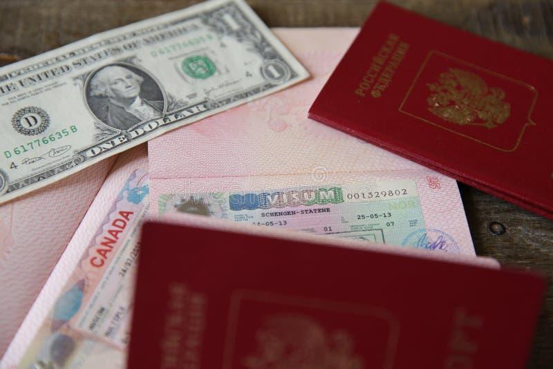 Passaporte do russo com um visto do canadense e do Schengen e dinheiro - um dólar Passaporte do curso do selo de visto F?rias e c fotos de stock