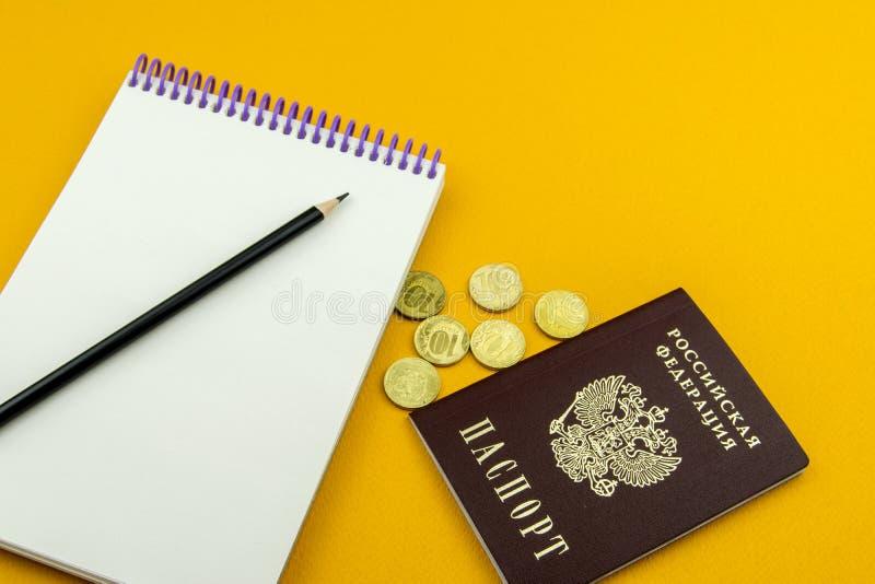 Passaporte do russo e diversas moedas Bloco de notas para entradas em um fundo alaranjado foto de stock royalty free