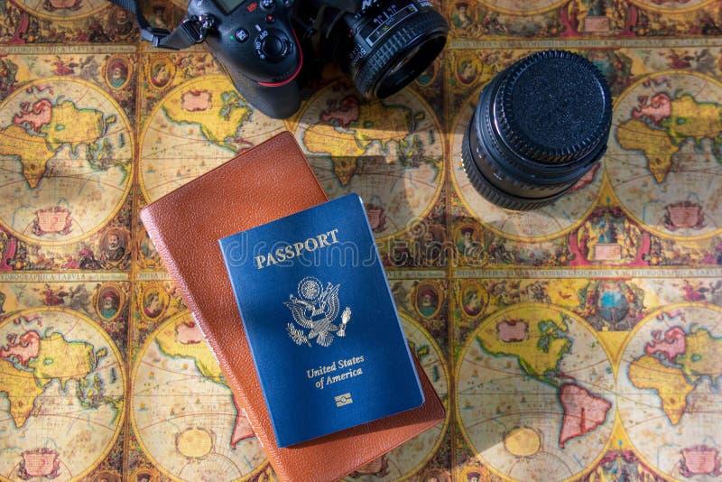 Passaporte e câmera do Estados Unidos no fundo do mapa do mundo fotografia de stock royalty free