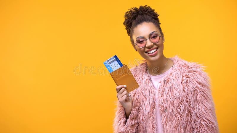 Passaporte guardando fêmea bonito com os bilhetes no fundo brilhante, aventura fotografia de stock royalty free