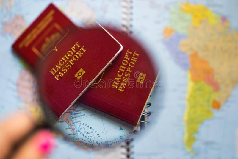 Passaporte sob o vidro da lupa no mapa do fundo do mundo fotografia de stock
