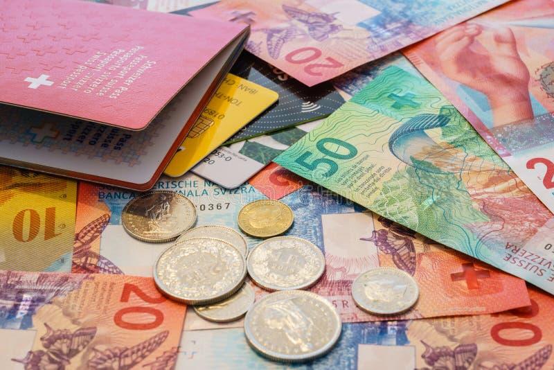 Passaporte suíço, cartões de crédito e francos suíços com 20 e 50 contas novas do franco suíço fotografia de stock