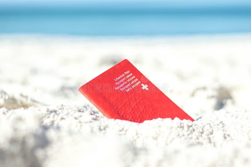 Passaporte suíço na areia na praia fotografia de stock