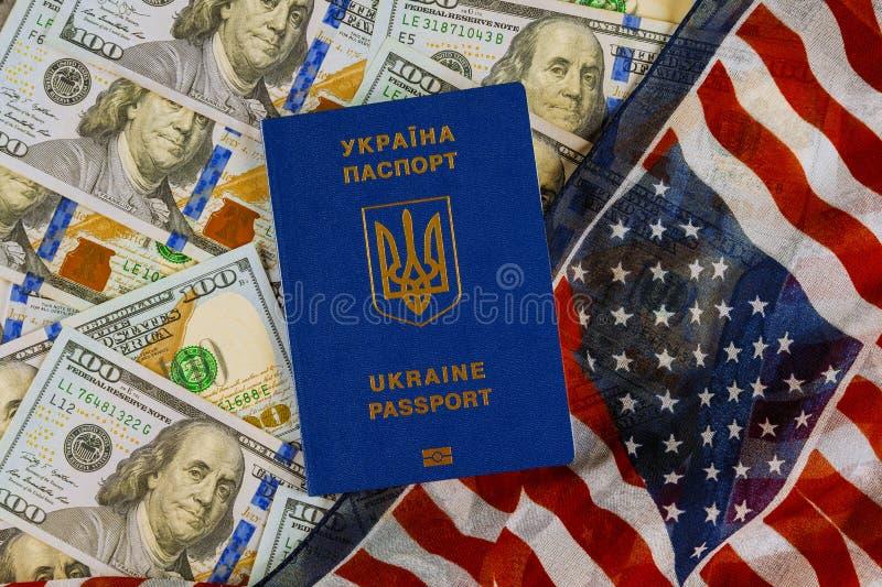 Passaporte ucraniano internacional em dólares americanos na bandeira nacional dos EUA fotografia de stock