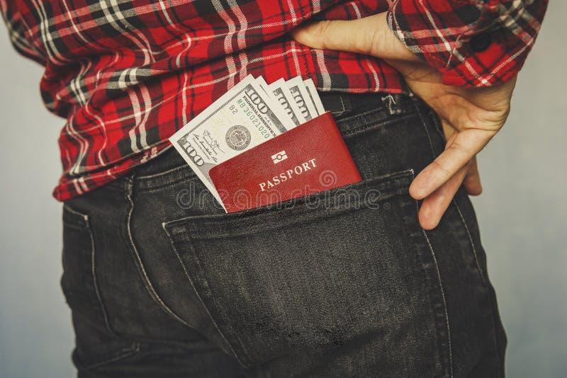 passaporte vermelho em um bolso das calças de brim imagem de stock royalty free