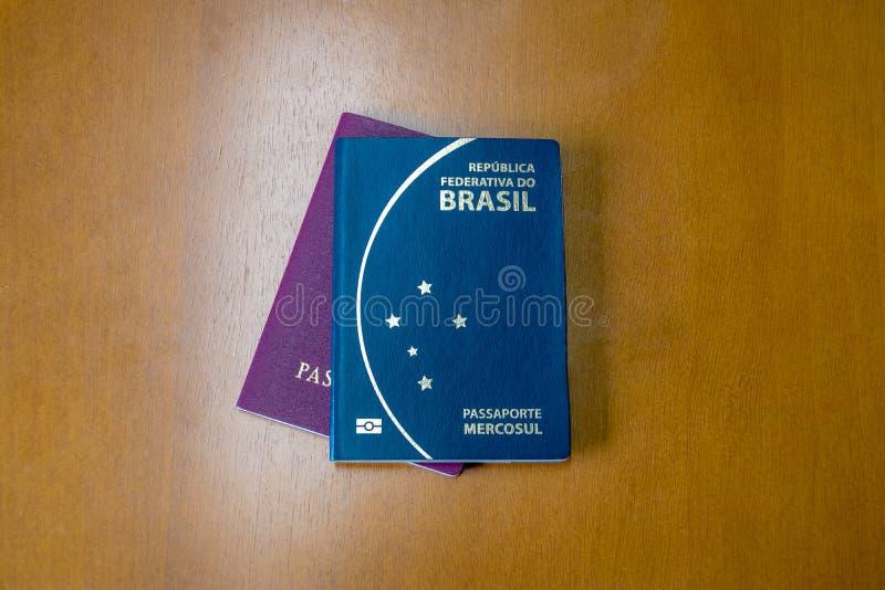 Passaportes brasileiros e europeus no fundo de madeira fotografia de stock royalty free