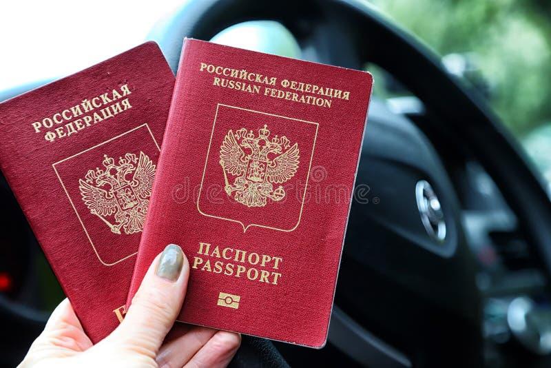 Passaportes do russo na mão da mulher e e do volante de um carro com uma paisagem borrada no fundo imagem de stock
