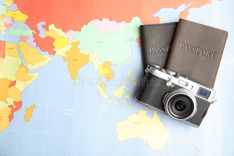 Passaportes e câmera no mapa do mundo, vista superior foto de stock