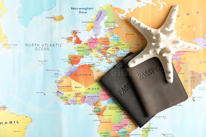 Passaportes e estrela de mar no mapa do mundo, vista superior fotografia de stock royalty free