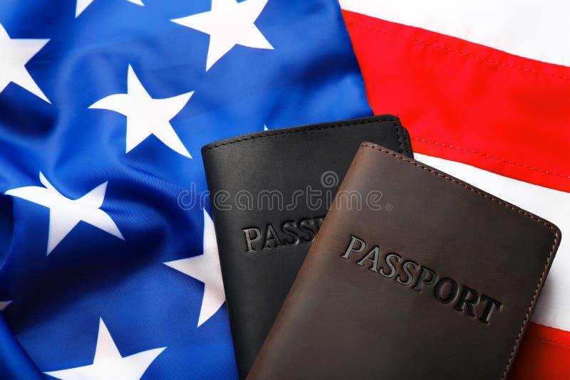Passaportes nas tampas de couro na bandeira dos EUA fotografia de stock