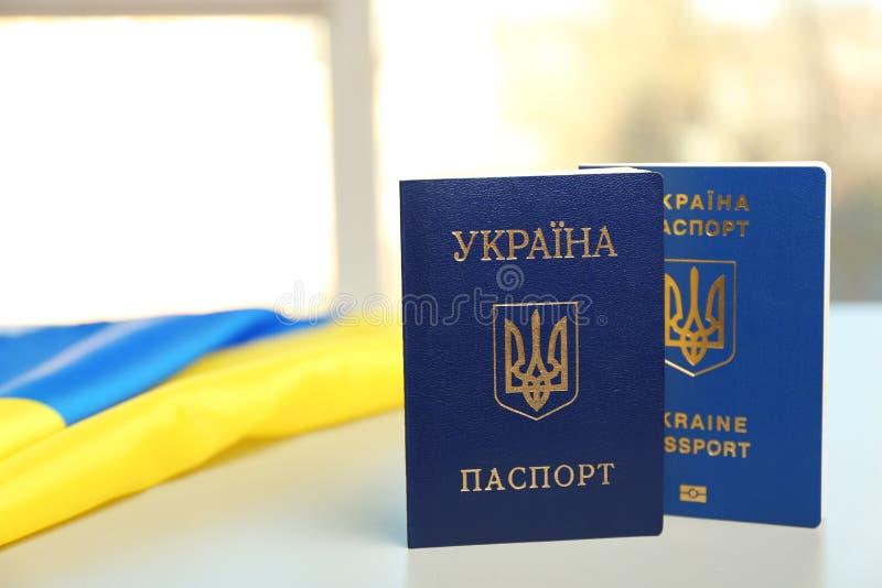 Passaportes ucranianos e bandeira nacional na tabela contra o fundo borrado r imagens de stock