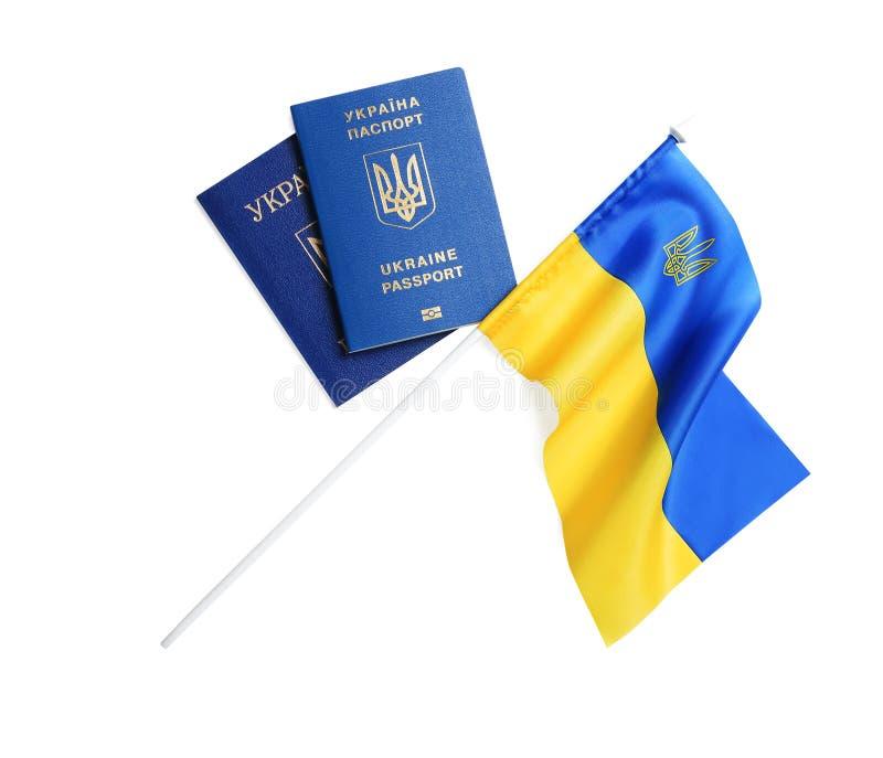 Passaportes ucranianos e bandeira nacional no fundo branco r fotografia de stock royalty free