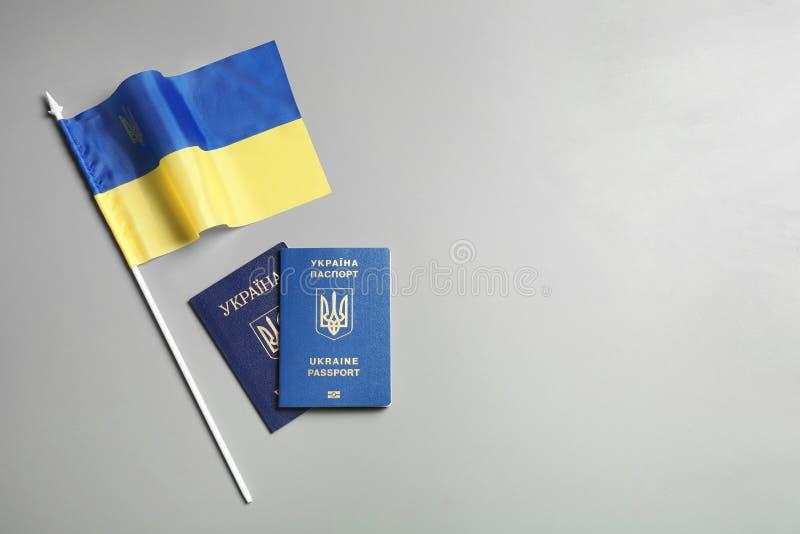 Passaportes ucranianos e bandeira nacional no fundo cinzento, vista superior r fotografia de stock