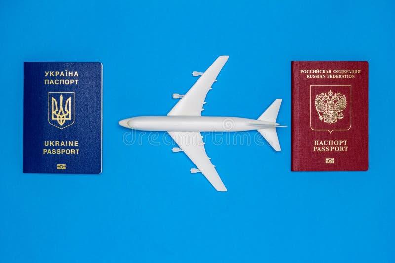 Passaportes ucranianos e do russo e modelos do avião O conceito da ressunção do tráfico aéreo entre países imagens de stock