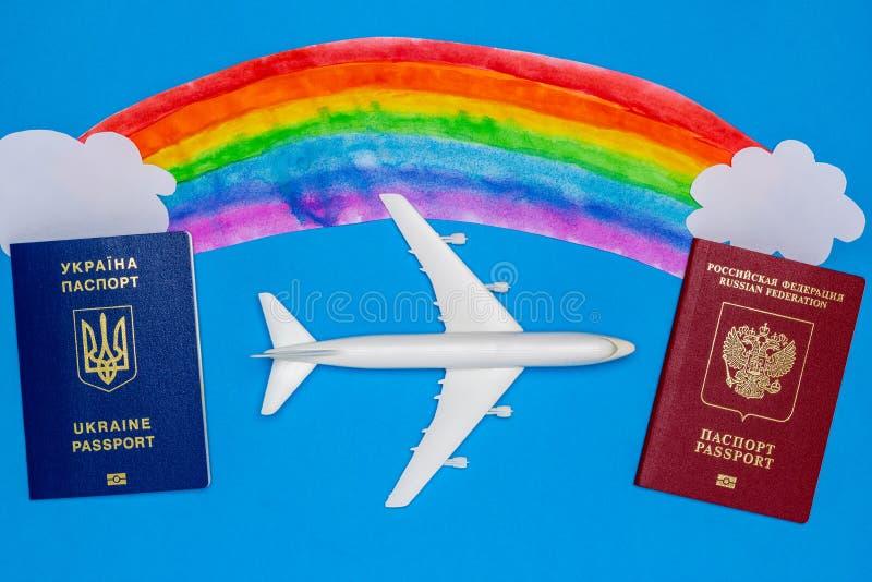 Passaportes ucranianos e do russo e modelos do avião O conceito da ressunção do tráfico aéreo entre países foto de stock royalty free