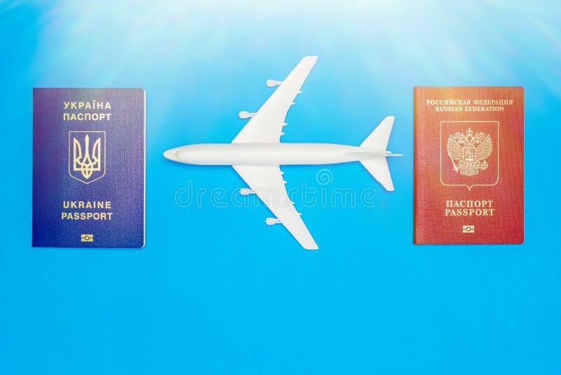 Passaportes ucranianos e do russo e modelos do avião O conceito da ressunção do tráfico aéreo entre países fotografia de stock