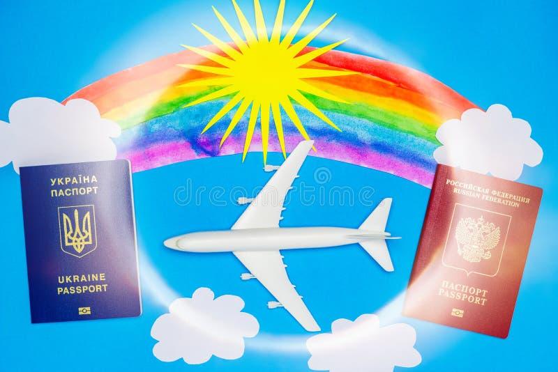 Passaportes ucranianos e do russo e modelos do avião O conceito da ressunção do tráfico aéreo entre países imagem de stock royalty free
