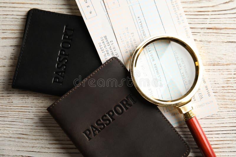Passaporti, biglietti e lente d'ingrandimento sulla tavola, vista superiore Agenzia di viaggi immagini stock libere da diritti