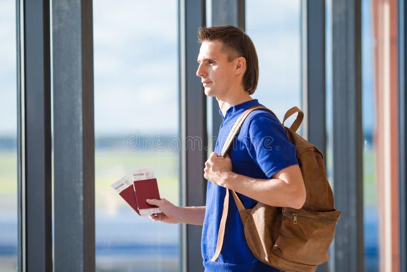 Passaporti della tenuta del giovane e passaggio di imbarco a immagini stock libere da diritti