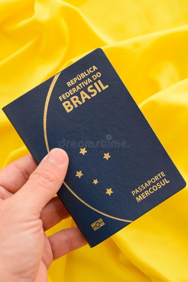 Passaporto brasiliano su tessuto giallo che rappresenta la bandiera brasiliana immagini stock
