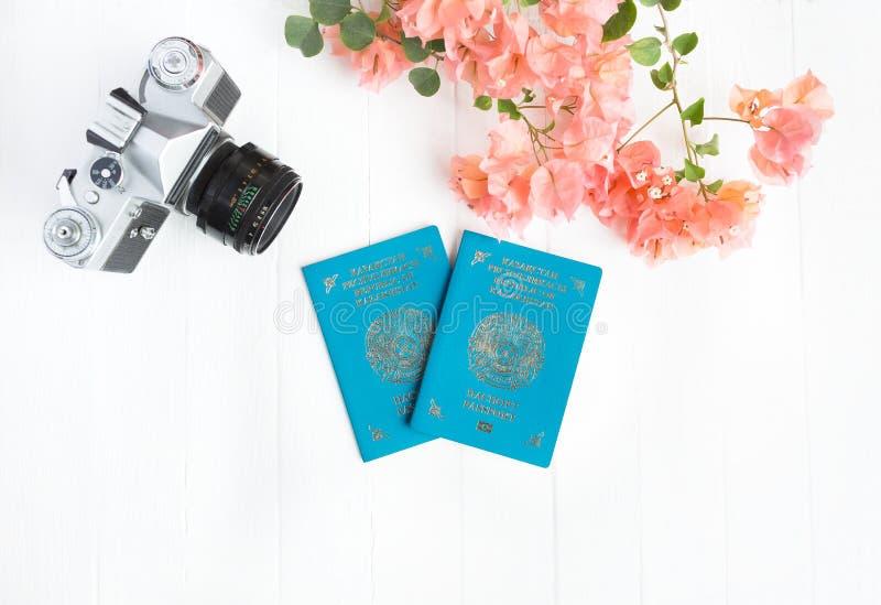 Passaporto del Kazakistan, macchina fotografica, buganvillea rosa su un fondo bianco Vista superiore immagine stock libera da diritti
