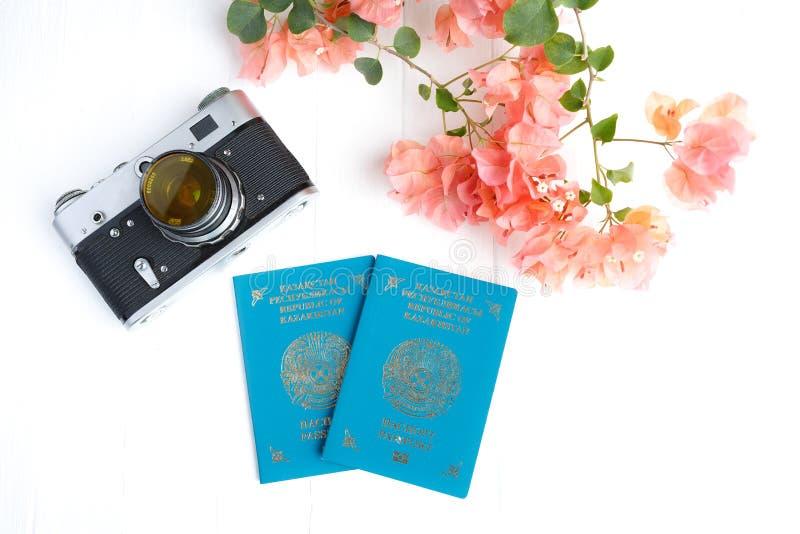 Passaporto del Kazakistan, macchina fotografica, buganvillea rosa su un fondo bianco Vista superiore immagine stock