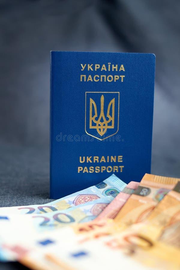 Passaporto dell'Ucraina con le euro fatture dentro Su un backgraund grigio fotografie stock libere da diritti