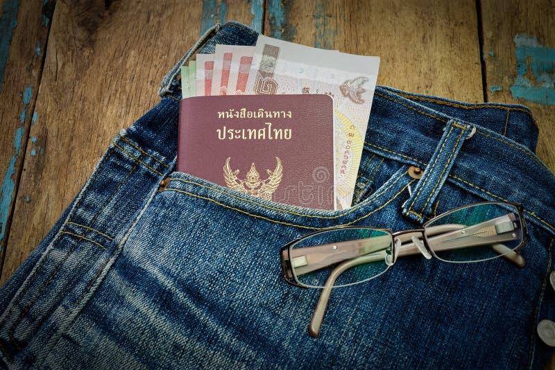 Passaporto e soldi sui jeans fotografie stock
