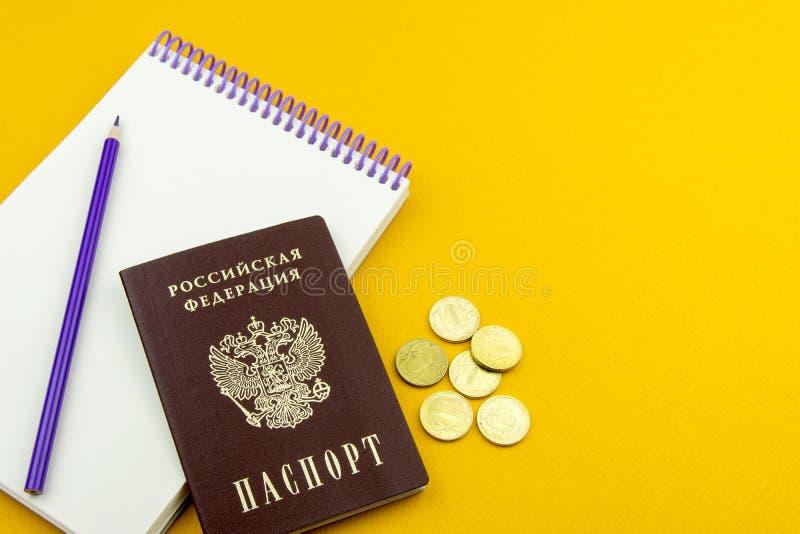 Passaporto russo e parecchie monete Blocco note per le entrate su un fondo arancio immagini stock