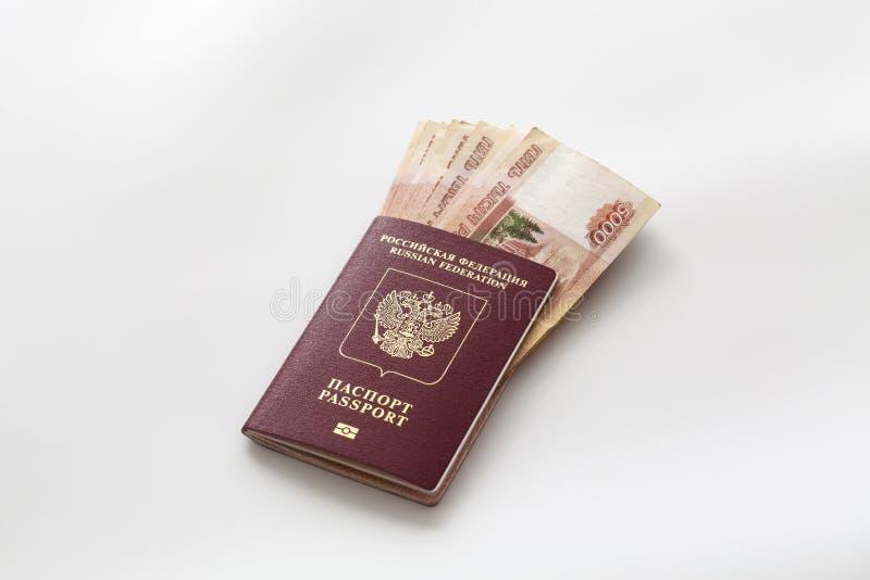Passaporto russo e un pacchetto di cinque millesime banconote della rublo Copertura straniera del passaporto in rosso e soldi rus immagine stock libera da diritti