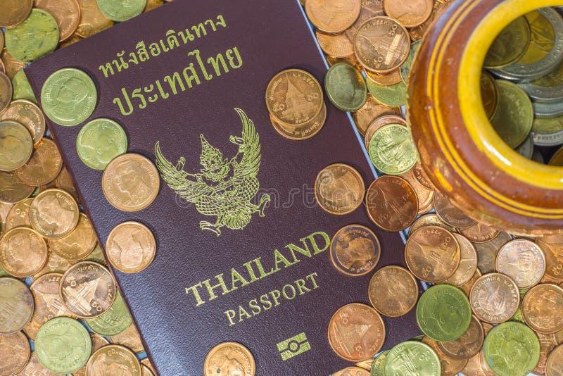 Passaporto tailandese su un mucchio delle monete immagini stock libere da diritti